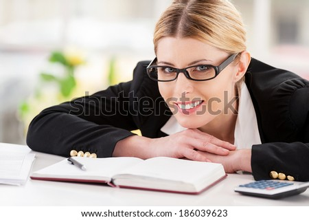 Confident business lady. Beautiful mature woman in formalwear looking over shoulder and smiling while sitting at her working place - stock photo