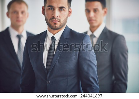Confident business leader looking at camera with two colleagues behind - stock photo