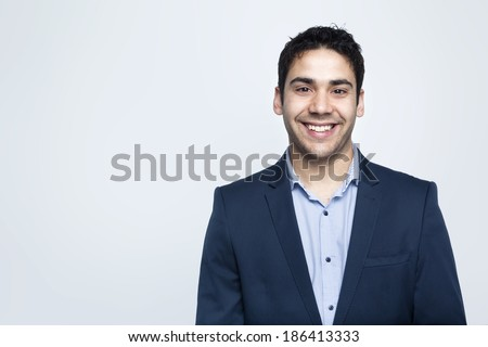 Confident business man smiling on grey background - stock photo