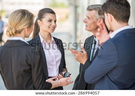 Confident business people discussing project while standing in front of office. - stock photo