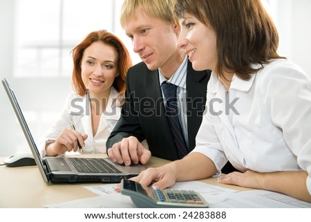 Confident business people doing some computer work together - stock photo