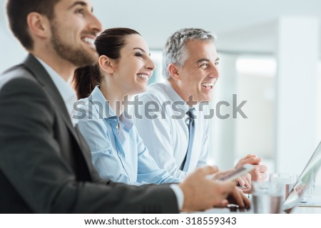 Confident business people team having a meeting in the office and smiling, office interior on background - stock photo