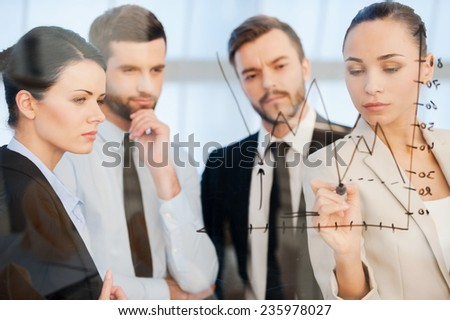 Confident business planning. Confident young businesswoman drawing a graph on glass while her colleagues standing near her and looking at sketch  - stock photo