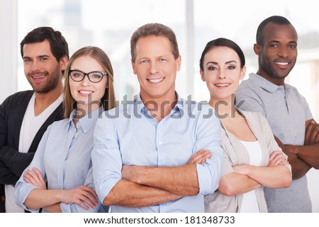 Confident business team. Group of cheerful business people in casual wear standing close to each other and keeping arms crossed - stock photo