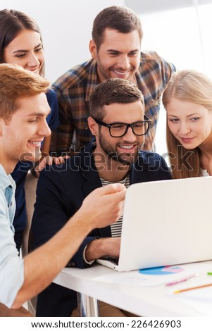 Confident business team. Group of cheerful business people in smart casual wear looking at the laptop together and smiling  - stock photo