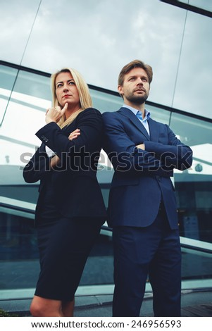 Confident business team of man and woman standing with crossed hands, team spirit concept, couple of success business people ready to act, business manager and employee,ready to implement plans - stock photo