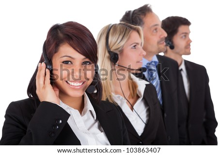 Confident business team with headset standing in a line against white background - stock photo
