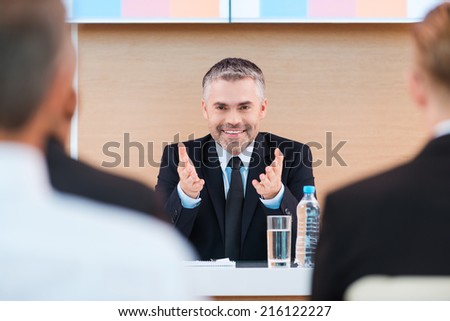 Confident business trainer. Cheerful mature man in formalwear making presentation in conference hall with people on the foreground - stock photo