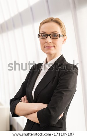 Confident business woman. Beautiful mature woman in formalwear keeping arms crossed and looking at camera - stock photo
