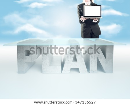 Confident business woman, standing near the PLAN table and holding a laptop - stock photo