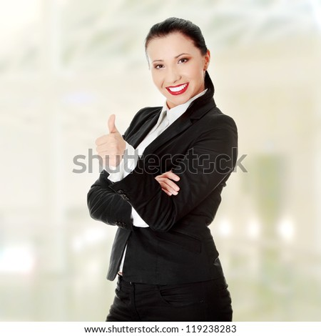 Confident business woman standing wearing elegant clothes with thumb up - stock photo