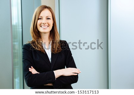 Confident business woman stands in the office - stock photo