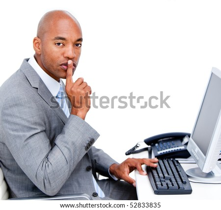 Confident businessman asking for silence sitting at his desk in the office - stock photo