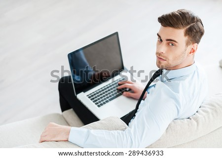 Confident businessman at work. Top view of confident young man working on laptop while sitting on sofa  - stock photo