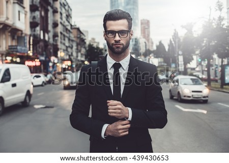 Confident businessman. Confident young man in full suit adjusting his sleeve and looking away while standing outdoors with cityscape in the background - stock photo