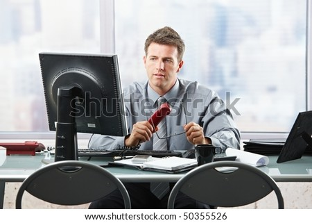 Confident businessman focusing on computer screen sitting at desk in office. - stock photo