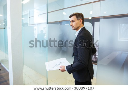 Confident businessman in formalwear holding documents and entering the office - stock photo