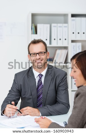 Confident businessman in his office seated at his desk working with a female colleague looking to to smile at the camera - stock photo