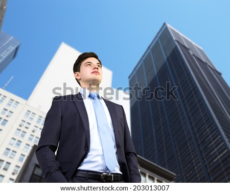 Confident businessman is looking to the future in a city view skyscrapers background - stock photo
