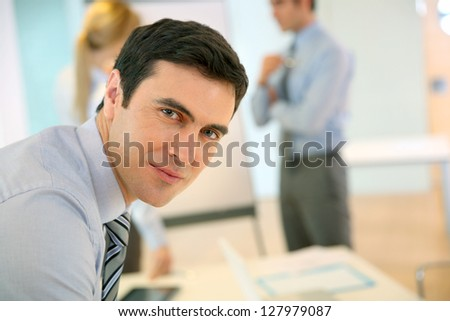 Confident businessman leaning on table - stock photo