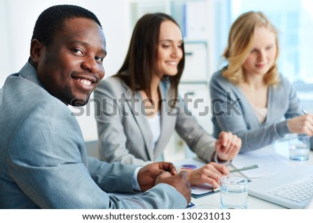 Confident businessman looking at camera with his two employees interacting on background - stock photo