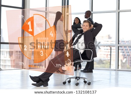 Confident businessman looking at orange pie chart interface with colleagues behind - stock photo