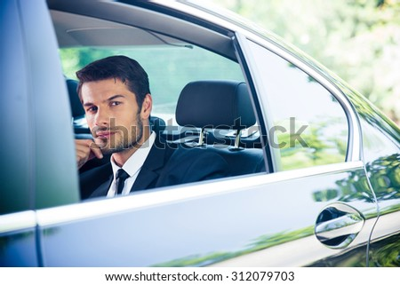 Confident businessman looking at window in car - stock photo