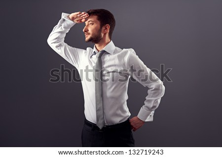confident businessman looking into the distance. studio shot over dark background - stock photo