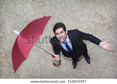 Confident businessman looking to the sky and checking if it's raining - stock photo