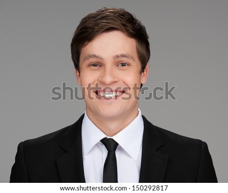 Confident businessman. Portrait of cheerful young businessman looking at camera while isolated on grey - stock photo