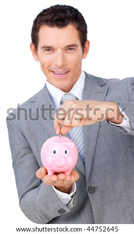 Confident businessman saving money in a piggy bank against a white background - stock photo