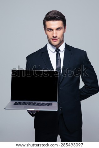 Confident businessman showing blank laptop screen over gray background. Looking at camera - stock photo