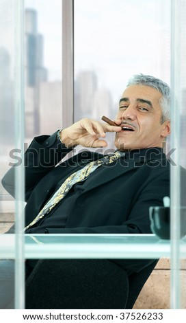 Confident businessman sitting at desk in front of office windows, leaning back, smoking cigar. - stock photo