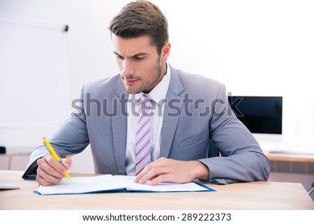 Confident businessman sitting at the table and signing document in office - stock photo
