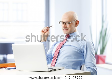 Confident businessman sitting in front of computer and thinking to solve the problem. - stock photo