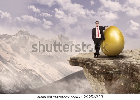 Confident businessman standing on top of a mountain beside golden egg - stock photo