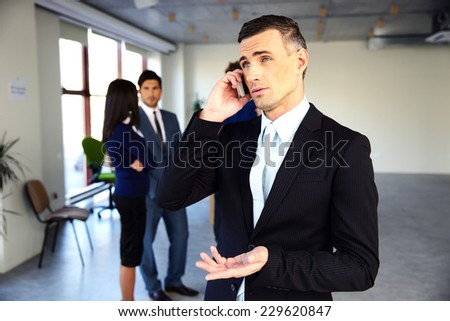Confident businessman talking on the phone in front of colleagues - stock photo