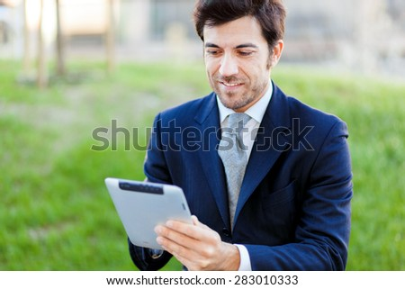 Confident businessman using a tablet outdoor - stock photo