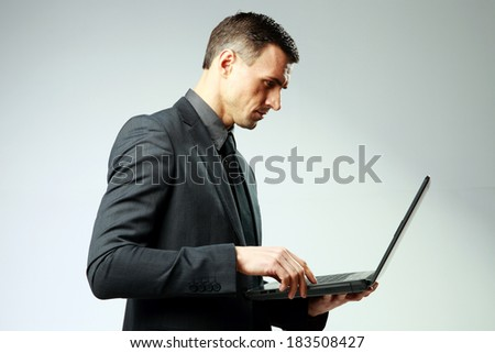 Confident businessman using laptop on gray background - stock photo