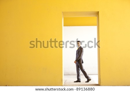 Confident businessman walking next to a yellow wall - stock photo