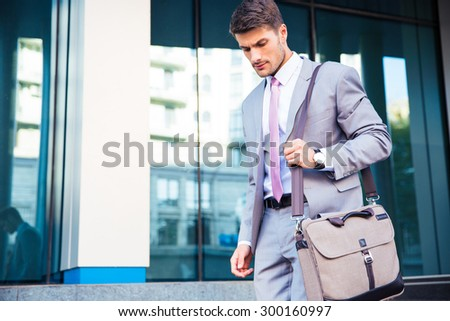 Confident businessman walking outdoors near office building - stock photo