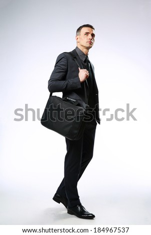 Confident businessman with bag looking up over gray background - stock photo