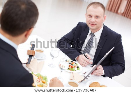 Confident businessman with clipboard looking at camera during paper discussion at business lunch - stock photo