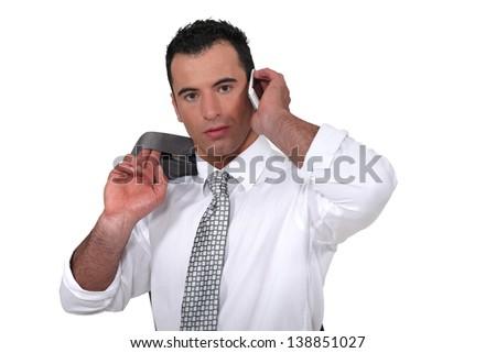 Confident businessman with jacket over shoulder - stock photo