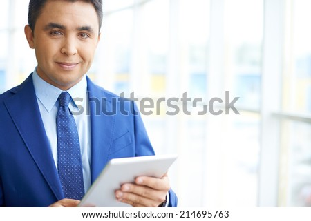 Confident businessman with touchpad looking at camera - stock photo