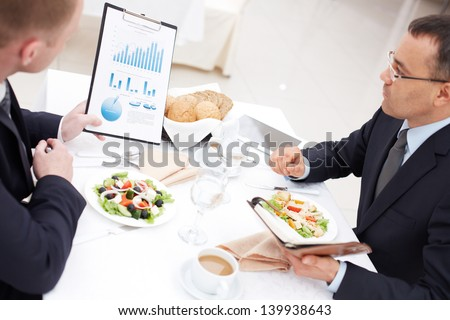 Confident businessmen discussing paper during business lunch - stock photo