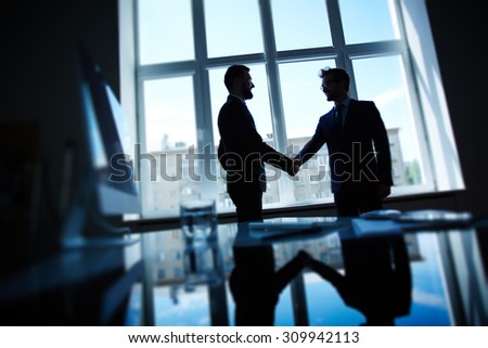 Confident businessmen handshaking after negotiations - stock photo