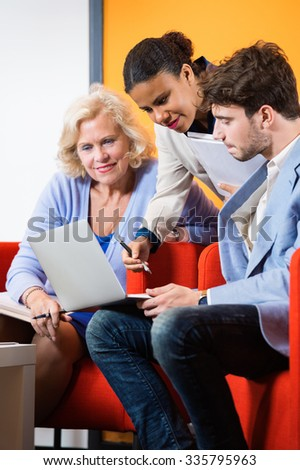 Confident businesspeople discussing over laptop in lobby at office - stock photo