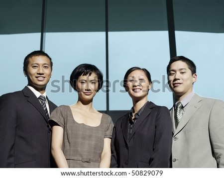 Confident Businesspeople group portrait, low angle view - stock photo