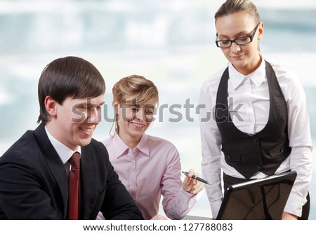 Confident businesspeople looking at laptop while briefing - stock photo